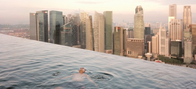 A man floats in the 57th-floor swimming pool of the Marina Bay Sands Hotel, with the skyline of Central,Σ the Singapore financial district, behind him. Singapore